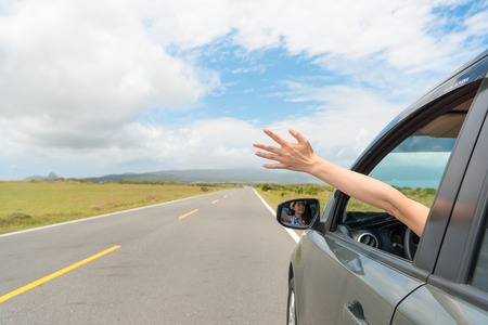 friendly girl sitting on travel car happily reach out hand enjoying own holiday vacation drove stopping on asphalt roadside viewing rural mountain scenery.