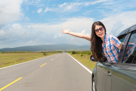 smiling woman wearing sunglasses happily make showing gestures sharing pastoral scenery in car window stopping on asphalt road at summer holiday. Фото со стока