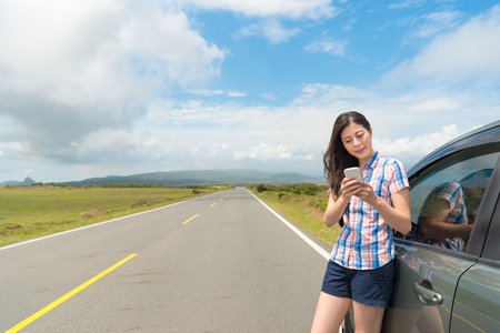 leisurely smiling female tourist using mobile smartphone searching online travel guidebook with car on asphalt roadside in road trip.