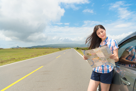 elegant pretty girl looking at paper map blowing breeze standing next to car reading local travel guide with asphalt road background. Stock Photo