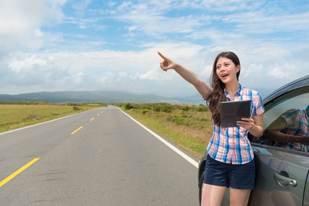 beautiful young girl happily pointing famous pastoral scenery and using mobile pad computer watching tour guide book with travel car on asphalt road. Фото со стока