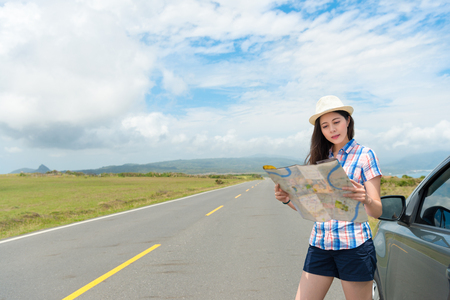 pretty young girl drive to countryside travel and car stopped at roadside standing on road looking paper map browsing local route.