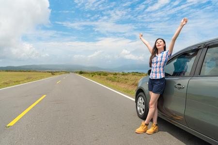 attractive happy female traveler standing on asphalt road raised hands enjoying rural countryside landscape ana travel car stopped at roadside.