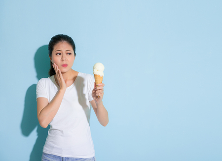 beauty cute female student suffering sensitive tooth disease looking at ice cream hesitate to eating in blue wall background.