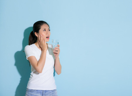 pretty elegant woman holding ice water hand on sensitive teeth part and looking at empty area thinking about solution standing in blue wall background. Foto de archivo