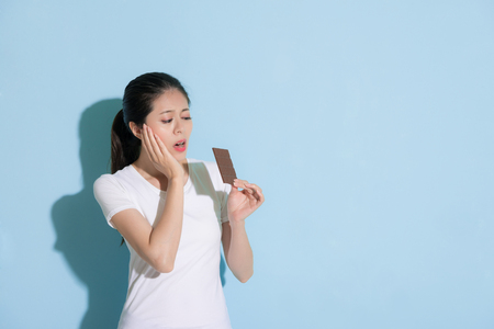 beauty young woman looking at chocolate cookie standing on blue wall background and feeling teeth painful because she having tooth decay problem.