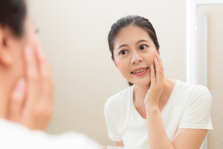 mirror image: sweet elegant female student standing in bathroom looking at mirror reflection image when wake up at morning maintain facial skin care.