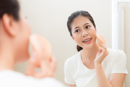 mirror image: beauty cute female model using cosmetic sponge makeup foundation on cheek in bathroom toilet at home with mirror reflection image.