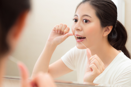 closeup photo of attractive elegant girl using floss clean tooth gap avoid remaining food on teeth with mirror reflection image in bathroom. Stock Photo