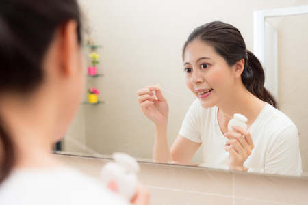 pretty sweet woman in bathroom at home looking at mirror reflection image and use floss clean teeth keep tooth healthy after eating.