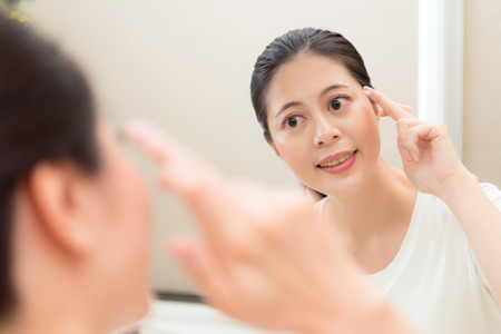 closeup photo of sweet pretty smiling girl bringing face cream on finger looking at mirror care cheeks in bathroom with reflection image. Stock Photo