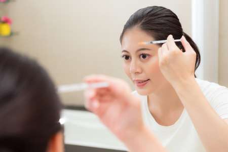 beautiful young woman receiving treatments with beauty procedure using syringe injections care medicine on forehead by herself in bathroom looking mirror.