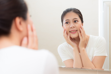 mirror image: pretty young girl looking at mirror reflection image hands holding on cheek smiling satisfaction face skin healthy situation in bathroom. Stock Photo