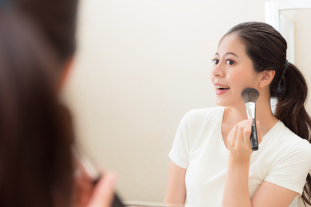 lovely beauty girl looking at mirror reflection image using makeup brush foundation and blush on face chin in bathroom at home. Stock Photo