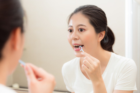 lovely young female model focus on mirror reflection image and using floss finishing teeth clean in bathroom after eating food. Stock Photo