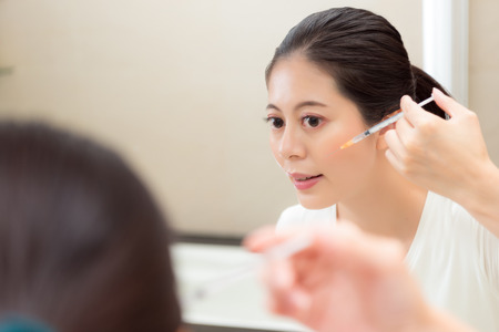 closeup portrait of young woman using syringe injection cosmetic care product standing in front of bathroom mirror looking at reflection image.