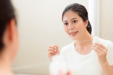 young beautiful female student holding floss standing in front of mirror looking at reflection image check teeth clean tidy on bathroom. Stock Photo