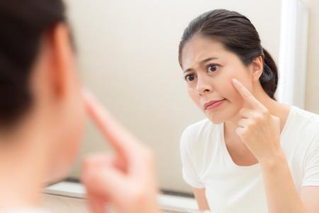 Jonge schattige vrouwelijke student vervelend gezicht met acne probleem tijdens de puberteit staan in de badkamer kijken naar spiegelreflectie afbeelding.