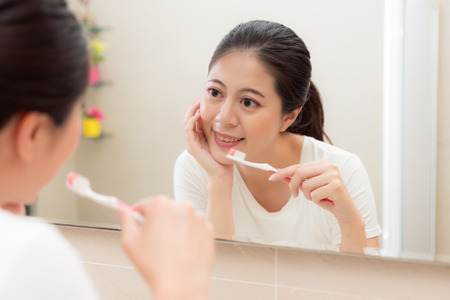 happy beautiful woman standing in front of bathroom mirror looking at mirror reflection smiling and using toothbrush ready brushing teeth at night.