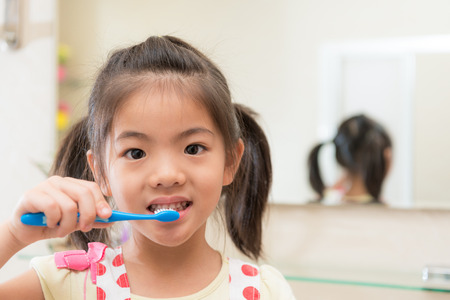 smiling lovely children girl using toothbrush cleaning teeth and face looking at camera with mirror reflection image background in bathroom at home.