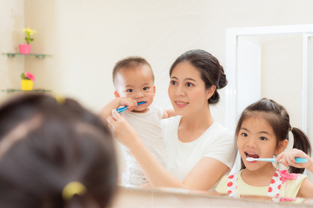 happiness family daily life photo of young mother with kid looking at mirror using toothbrush cleaning teeth in bathroom together every morning and night.