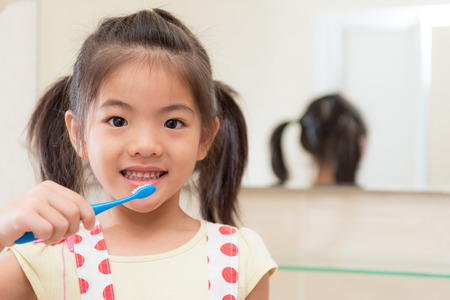 beautiful youth kid daughter holding children toothbrush standing in front of bathroom mirror and face to camera ready cleaning teeth at home.