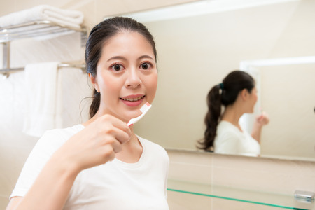 smiling young mother holding toothbrush face to camera showing teeth healthy concept in bathroom with mirror reflection image.