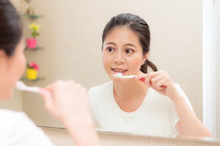 young smiling housewife using toothbrush cleaning teeth after eating food or waking up in morning standing on bathroom looking mirror brushing.