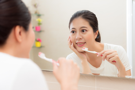 sweet smiling holding toothbrush and hand put on chin looking at mirror reflection image viewing face skin feeling happy in bathroom at home.