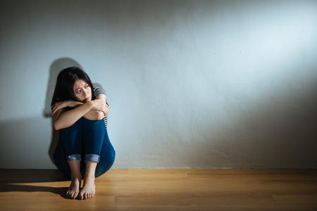 悲しみの絶望女の子は、ボロボロの虐待女性の概念を示す暗い白の背景の部屋で木製の床に座っていることを恐れて光の感じを見て.