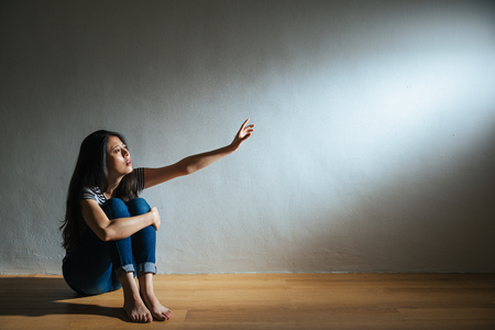 battered abused woman concept of lonely victim sitting on white background wood floor in dark and sadness looking at light need help. Foto de archivo