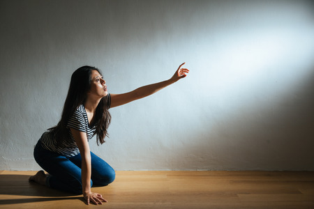 depression lady kneeling on wooden floor ground and reach out hand to light empty area searching helping on white wall background with battered abused woman concept.