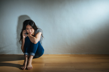 battered abused women concept of crying depair young girl sitting on wood floor using mobile phone calling talking friend having violence encounter in dark white wall background room.