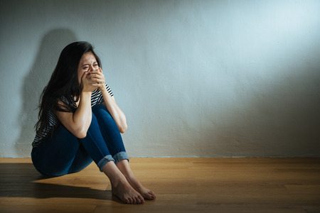 battered abused women concept of depressed woman sitting on wood floor in dark white wall room crying and hand cover mouth sadness feeling afraid.