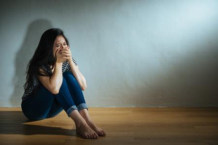 mishandelde misbruikte vrouwen concept van depressieve vrouw zittend op de houten vloer in de donkere witte muur kamer huilen en handbedekking mond droefheid bang voelen.