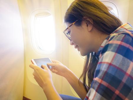 schoonheid lachende vrouwelijke passagier zitten in de buurt van stoel van het venster met mobiele mobiele telefoon spel als ze nemen vliegtuig gevoel saai. Stockfoto