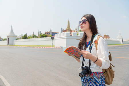 young woman tourist holding travel guide book and searching destination location in Bangkok, Thailand travel on famous grand palace roadside.
