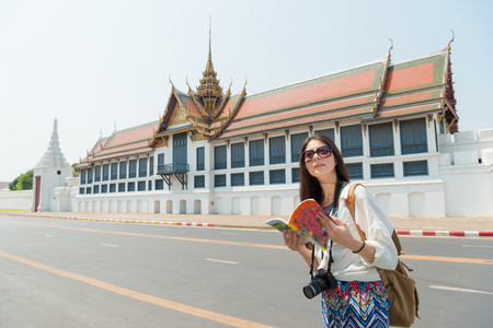 beautiful elegance female traveler visiting Bangkok famous grand palace and holding travel guidebook viewing culture information in Thailand travel vacation.