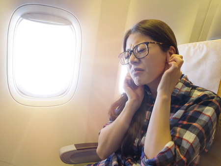 lovely sweet female traveler feeling ear painful when airplane take off getting tinnitus. Stok Fotoğraf - 85314512