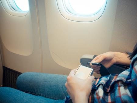 빈티지 복고 필름 색상으로 비행하는 동안 안전에 자신을 보호하기 위해 안전 벨트를 사용 하여 비행기를 타고 여성 여행자의 근접 촬영 사진.