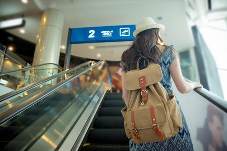 다시보기 사진 뷰어 여성 백패커 공항 에스컬레이터에 서 서 그녀가 도착했을 때 풍경보기 빈티지 복고 필름 색상 여행 역.