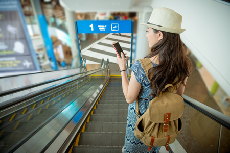 vintage retro film kleur. lachende mooie vrouwelijke reiziger met behulp van mobiele smartphone zoeken reisgids en neem de vliegtuig elektrische roltrap met back view foto.