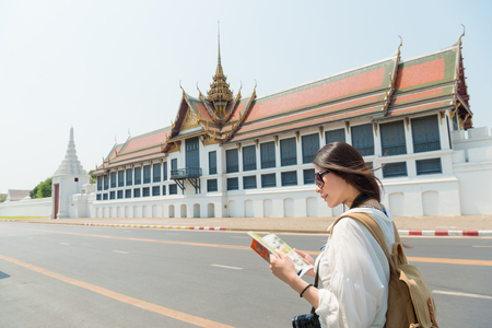 smiling pretty tourist woman reading travel guidebook standing on grand palace roadside searching information map in Bangkok, Thailand travel.