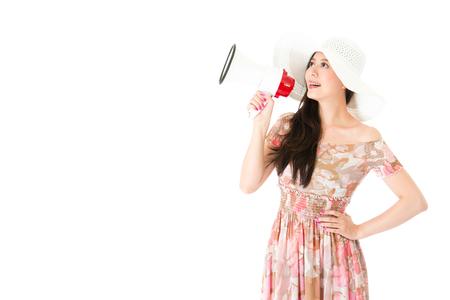 魅力的なエレガントなドレスの女性は、ホワイトの背景に立っているスピーカーを保持し、空の領域は、情報を発表しました。