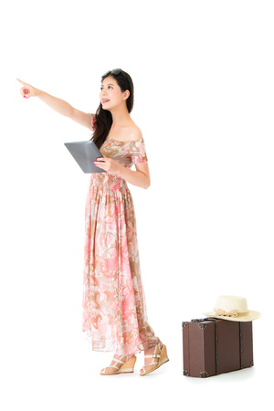 young pretty woman pointing empty area standing on white background with vintage suitcase and wearing summer travel dress clothing holding mobile digital tablet.