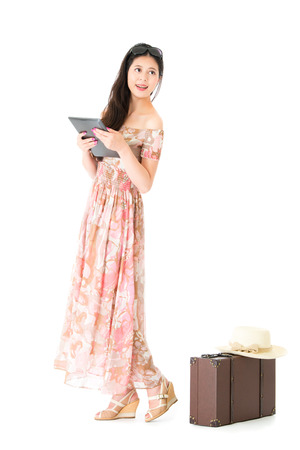 happy beautiful woman traveler looking at empty area thinking travel planning and holding mobile pad computer standing on white background with vintage suitcase.