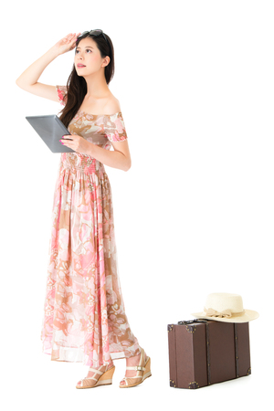 happy attractive traveler standing on white background with vintage luggage case and holding mobile pad computer thinking for travel planning.