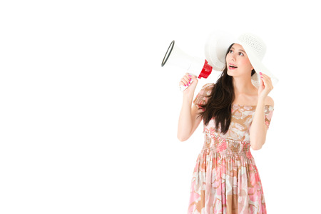 smiling elegant woman wearing dress standing on white background and holding megaphone looking at empty area daydreaming.