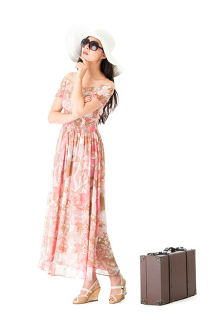 attractive beauty girl standing on white background with vintage baggage case and wearing summer clothing looking at empty area thinking travel planning.