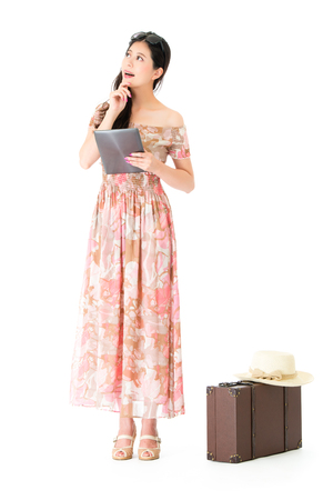 cheerful pretty lady standing on white background with retro style luggage suitcase and using mobile digital tablet planning travel. Stock Photo
